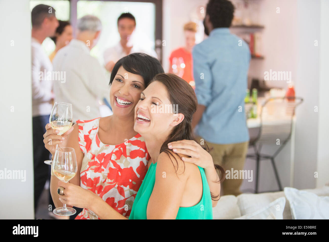 Women hugging at party - Stock Image