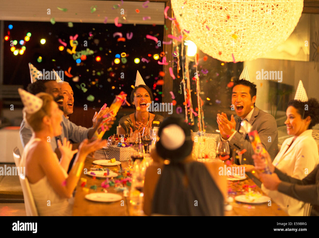 Friends throwing confetti at birthday party - Stock Image