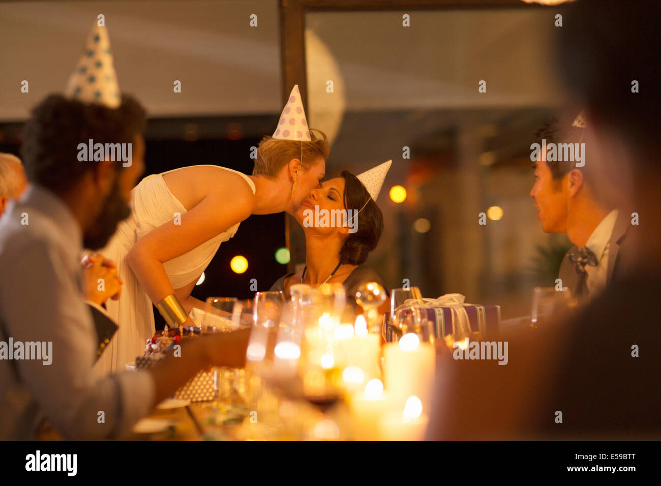 Woman kissing friend's cheek at birthday party - Stock Image