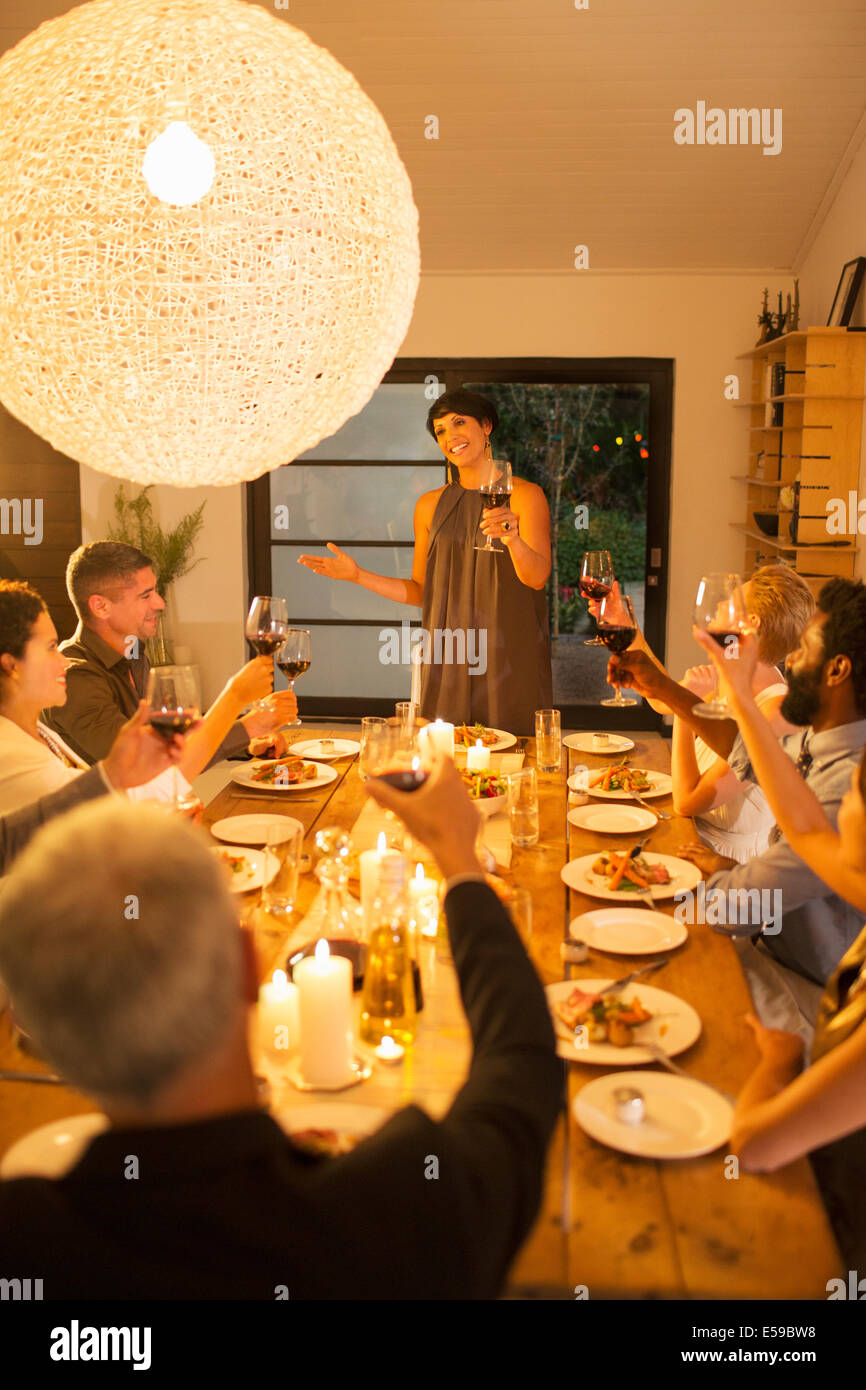 Woman giving toast at dinner party - Stock Image