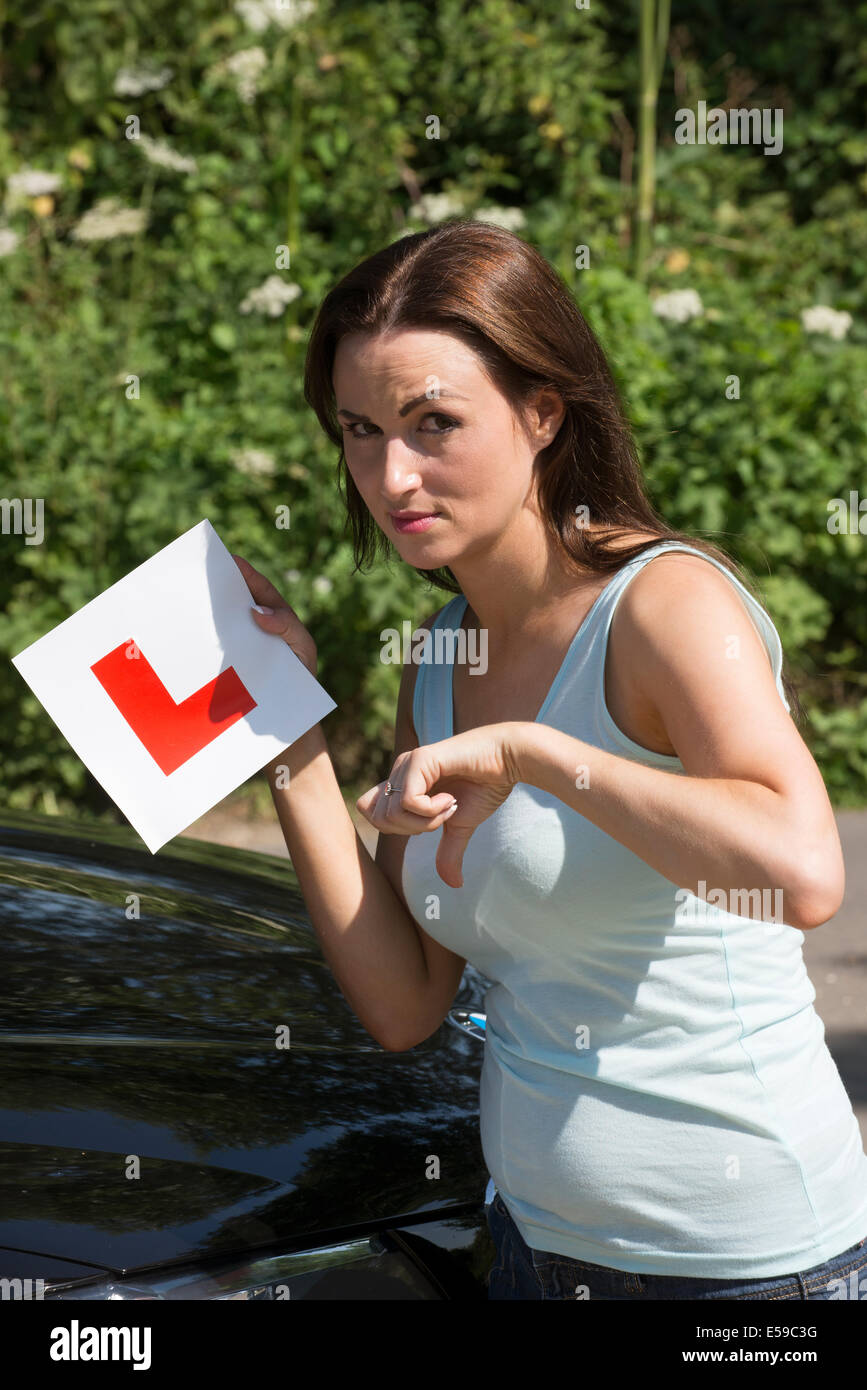 Woman driver holding L plate and thumbs down for a failure driving test result. - Stock Image