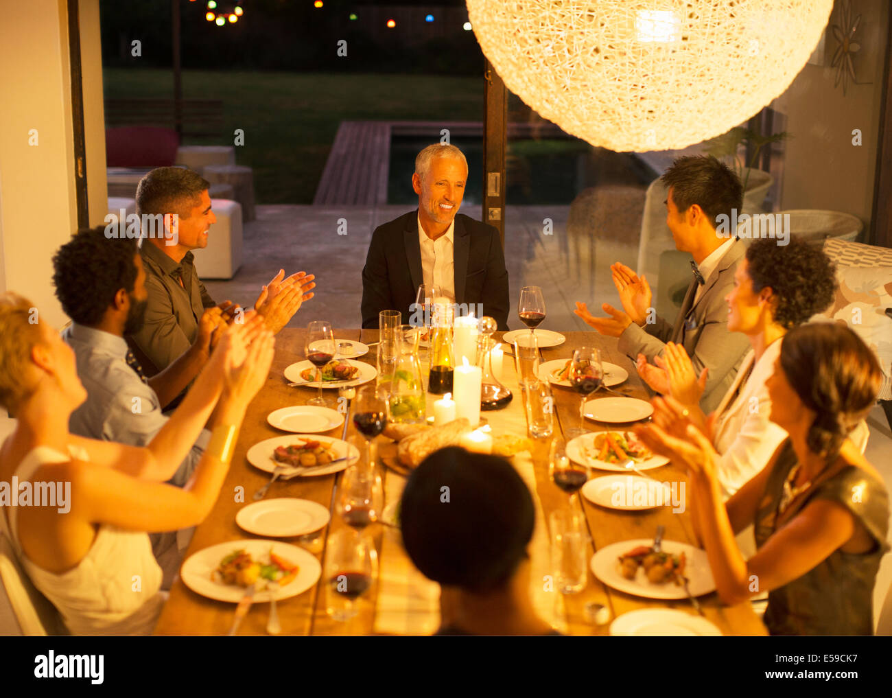 Friends applauding man at dinner party Stock Photo