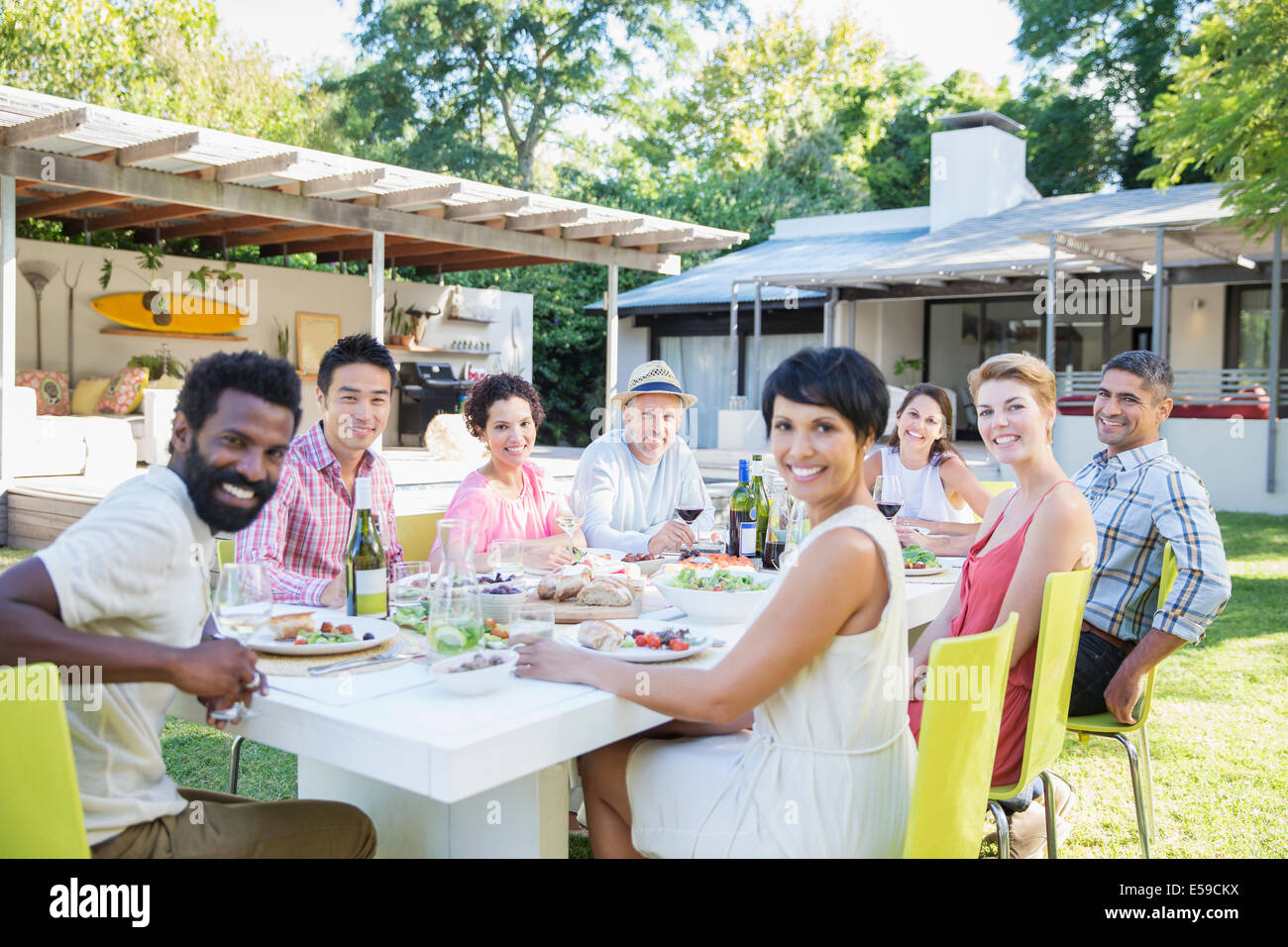 Friends smiling at table outdoors - Stock Image