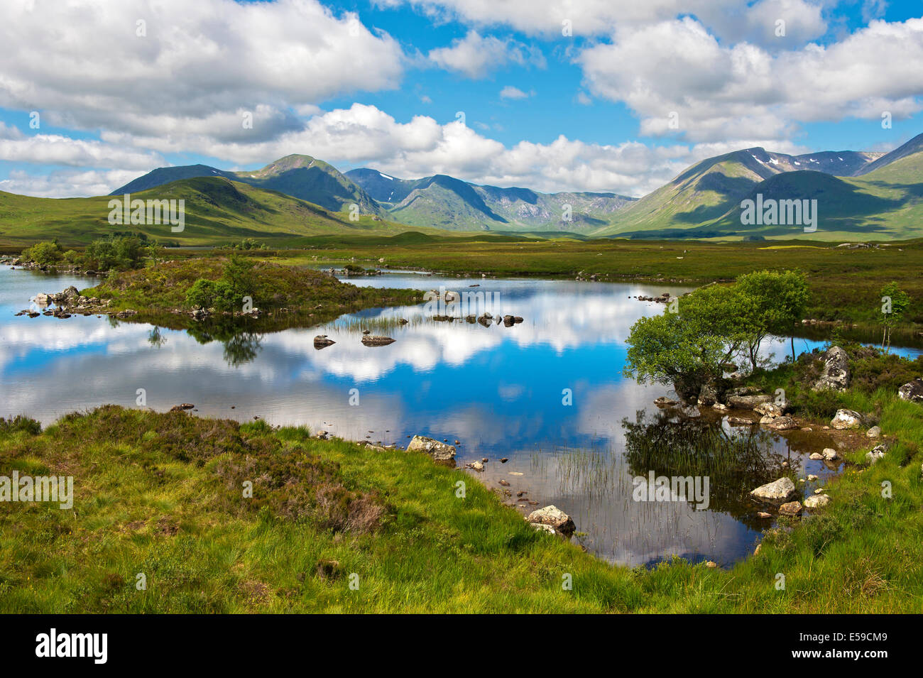 Cumulus clouds reflecting in a lake in the Scottish Highlands, Glencoe, Scotland, Great Britain - Stock Image