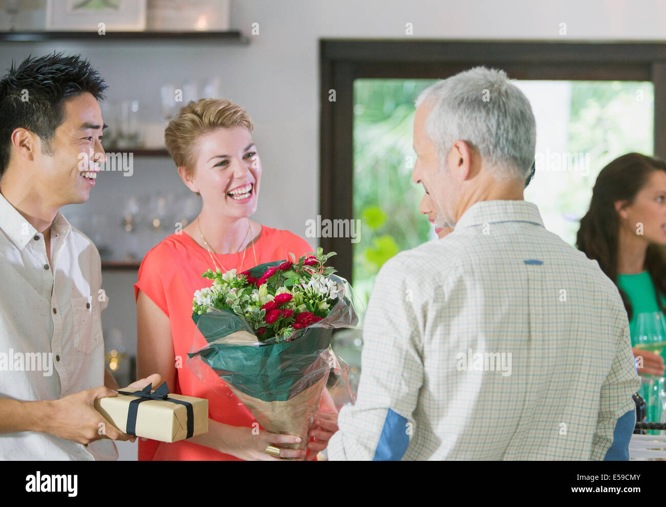 Friends exchanging gifts at party - Stock Image