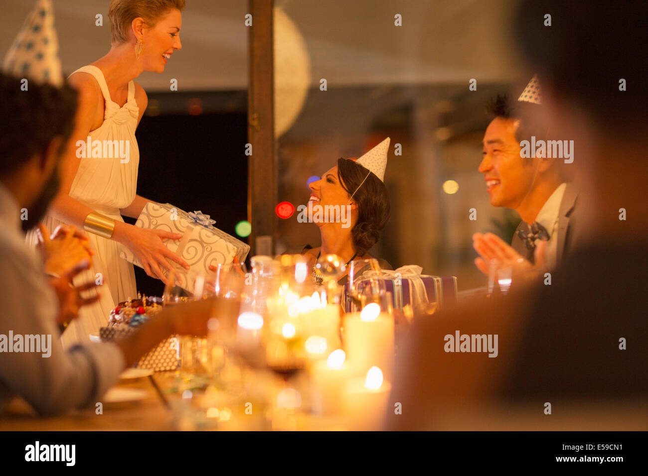 Woman giving friend present at birthday party - Stock Image