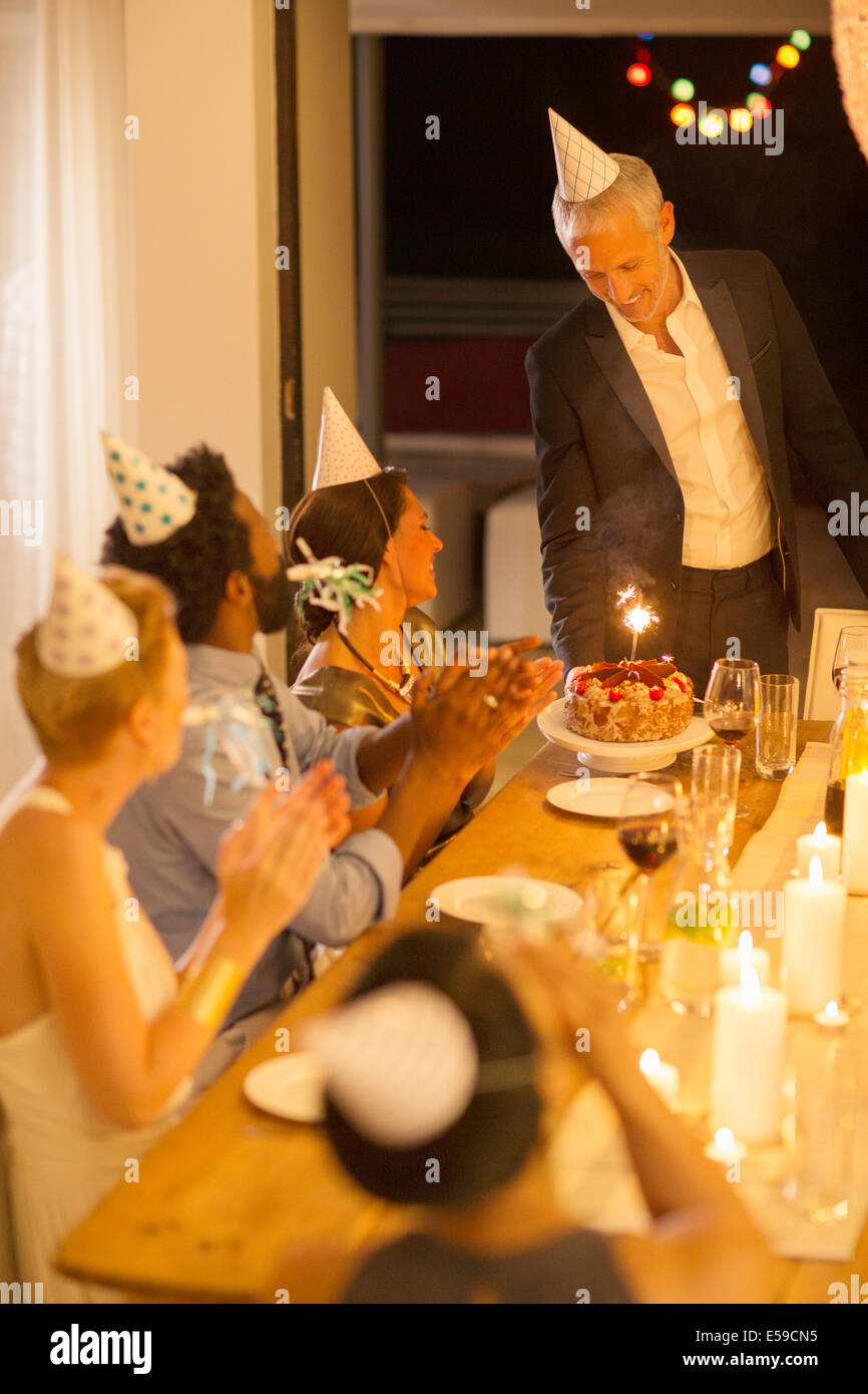 Man serving birthday cake at party - Stock Image