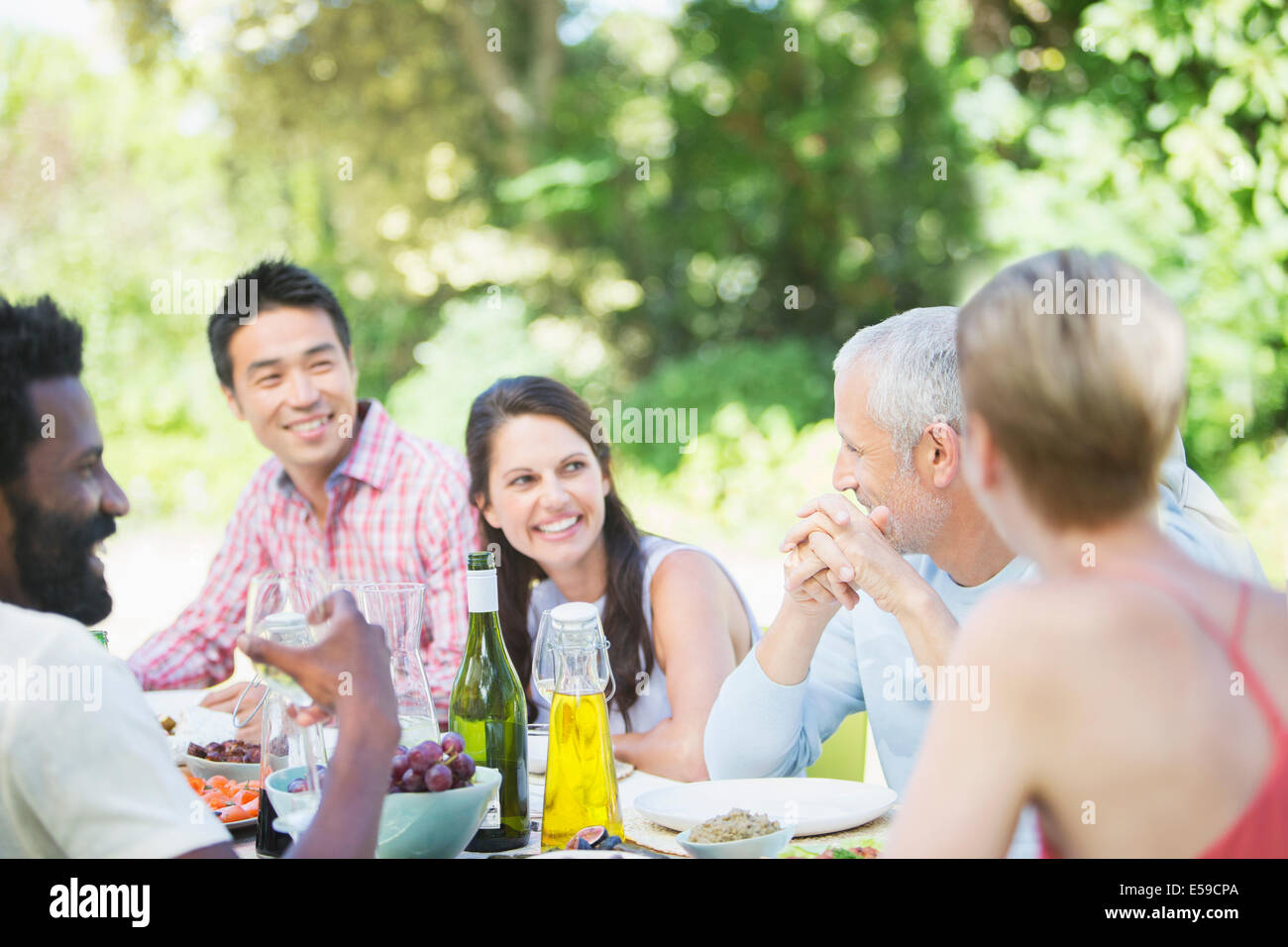 Friends talking at table outdoors - Stock Image