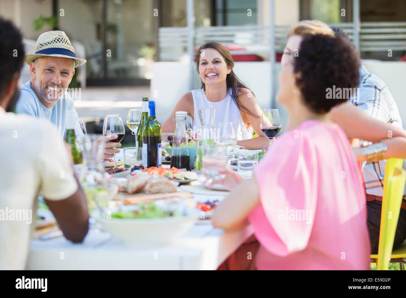 Friends relaxing at table outdoors - Stock Image