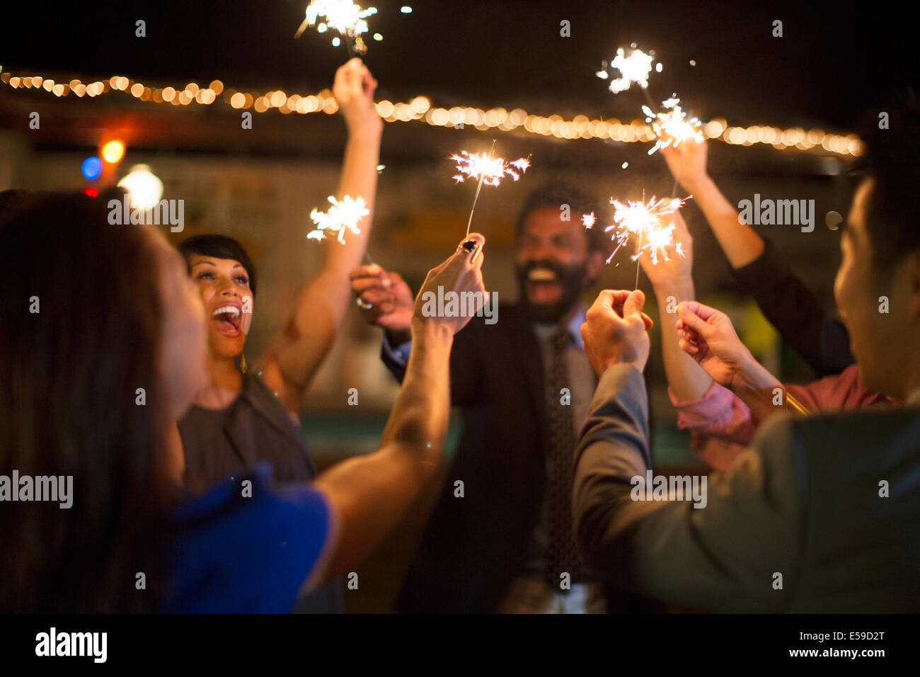 Friends playing with sparklers at party - Stock Image