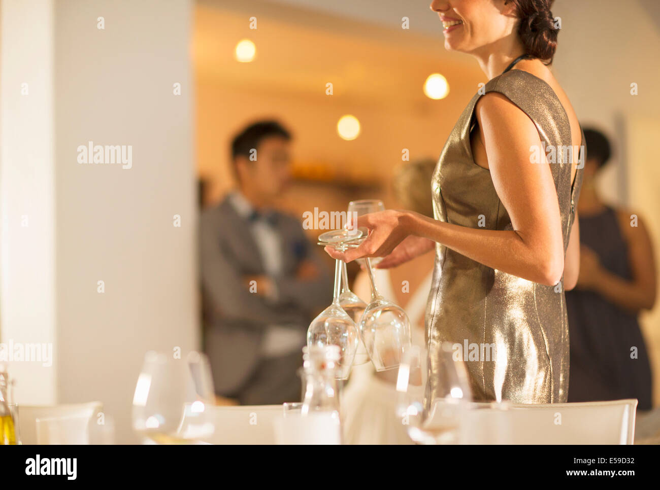 Woman setting table at dinner party Stock Photo