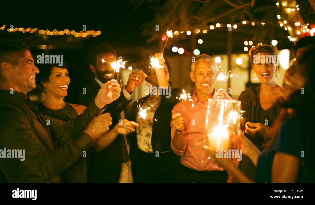 Friends playing with sparklers at party Stock Photo