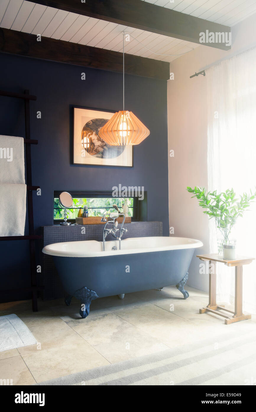 Bathtub and light fixture in modern bathroom - Stock Image