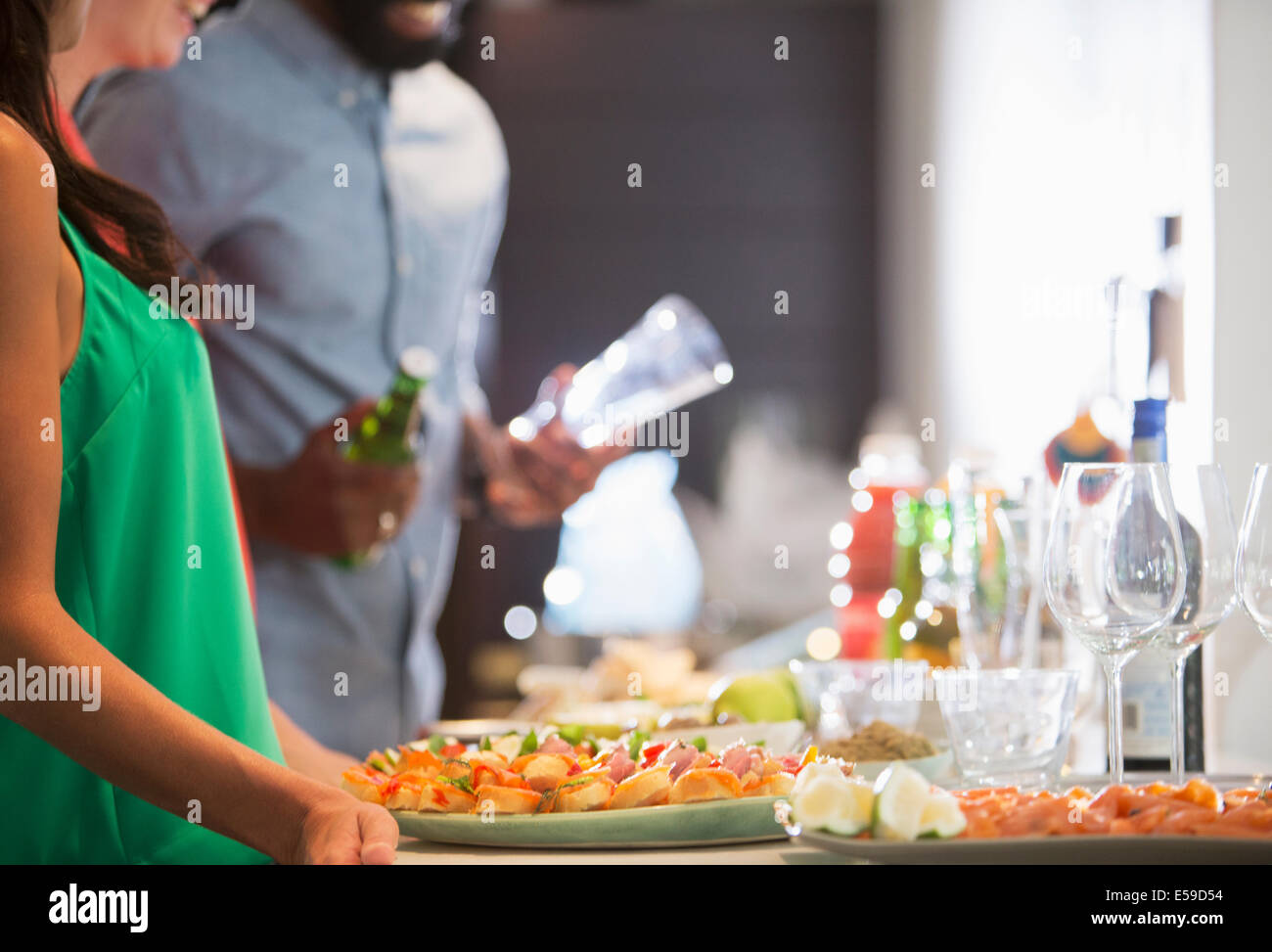 Woman with plates of food at party - Stock Image