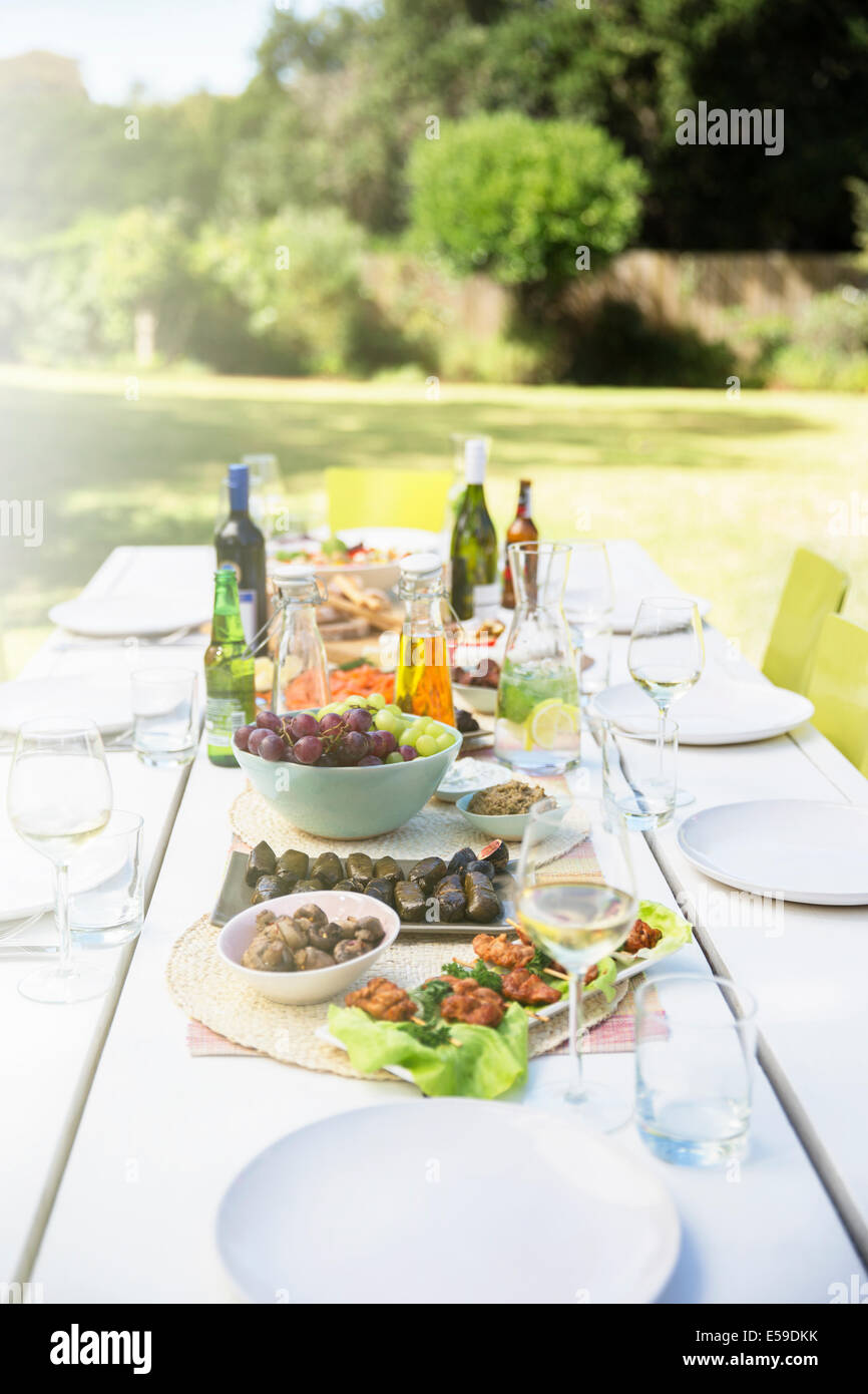 Plates of food on table outdoors - Stock Image