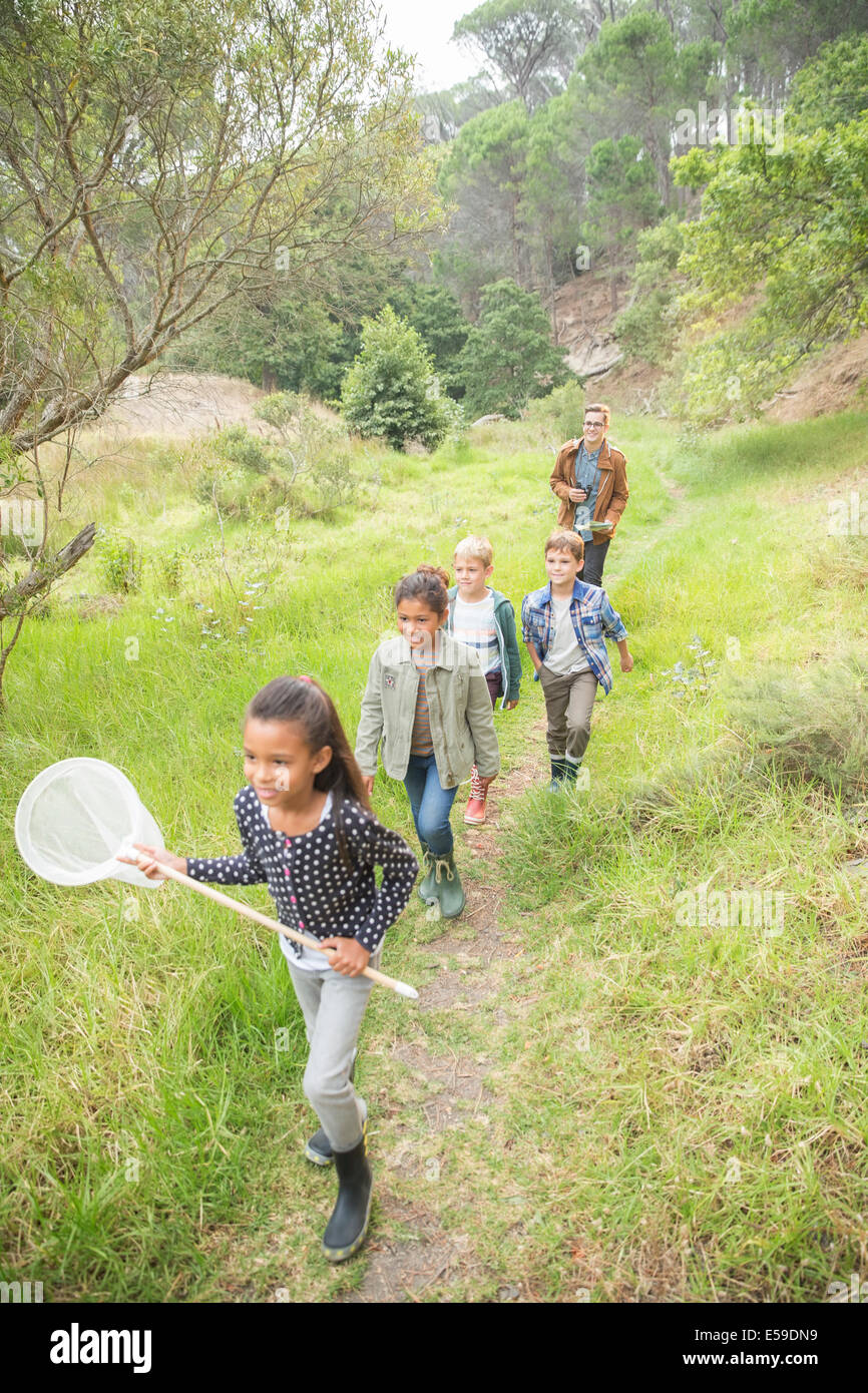 Students and teacher walking on dirt path - Stock Image