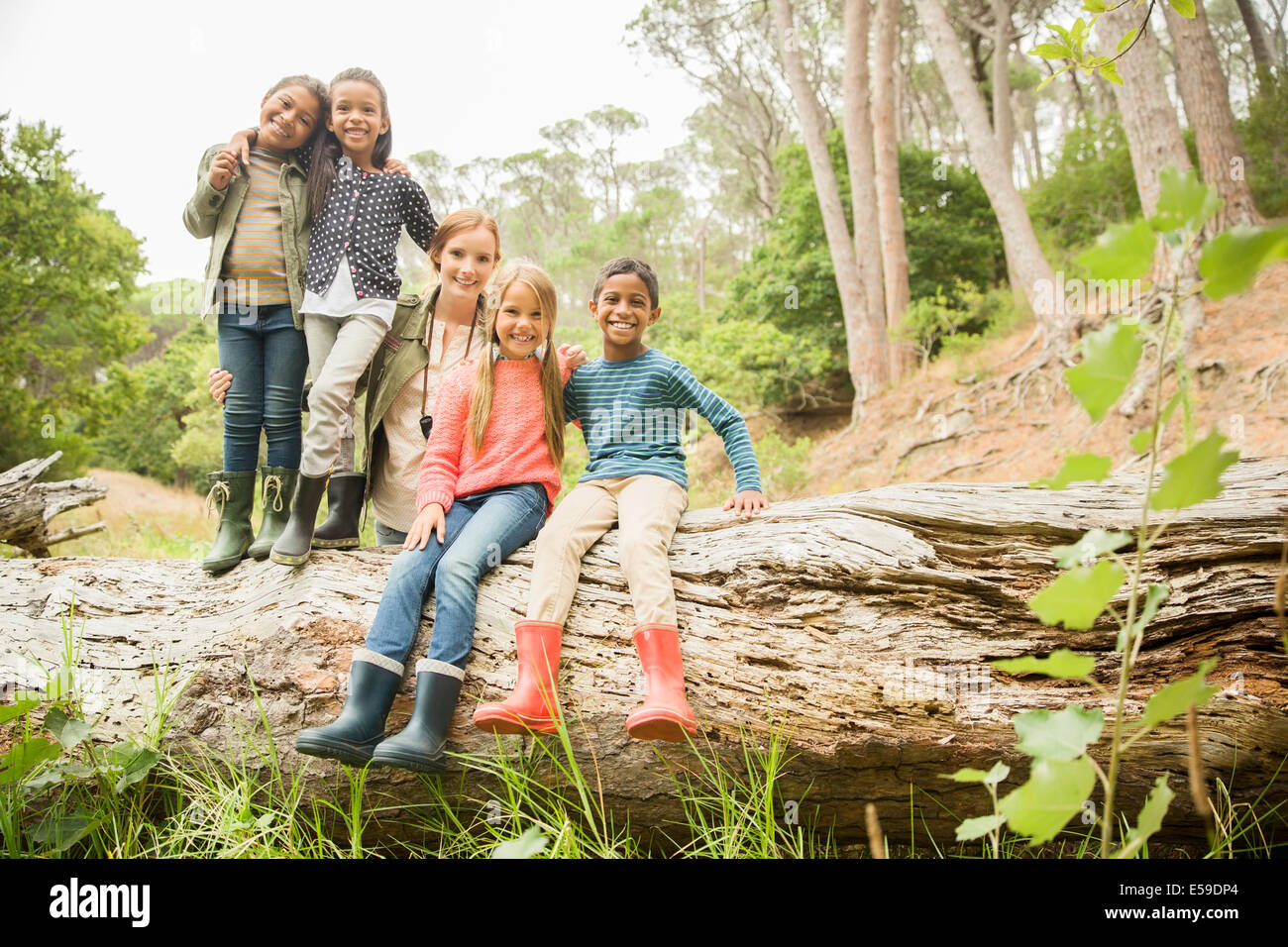 Students and teacher sitting on log in forest - Stock Image
