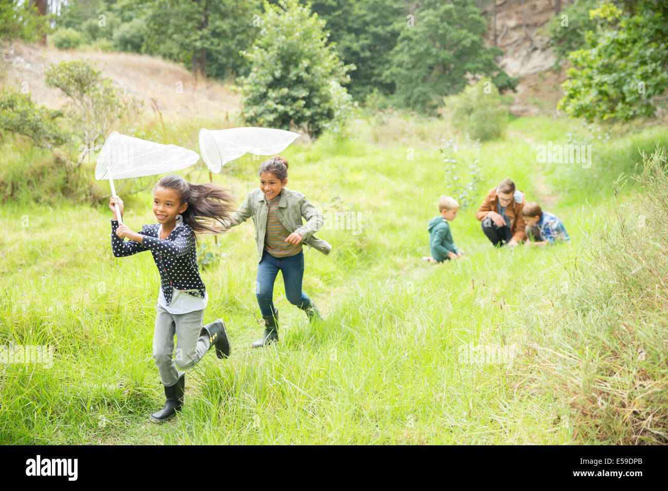 Children playing with butterfly nets on dirt path - Stock Image