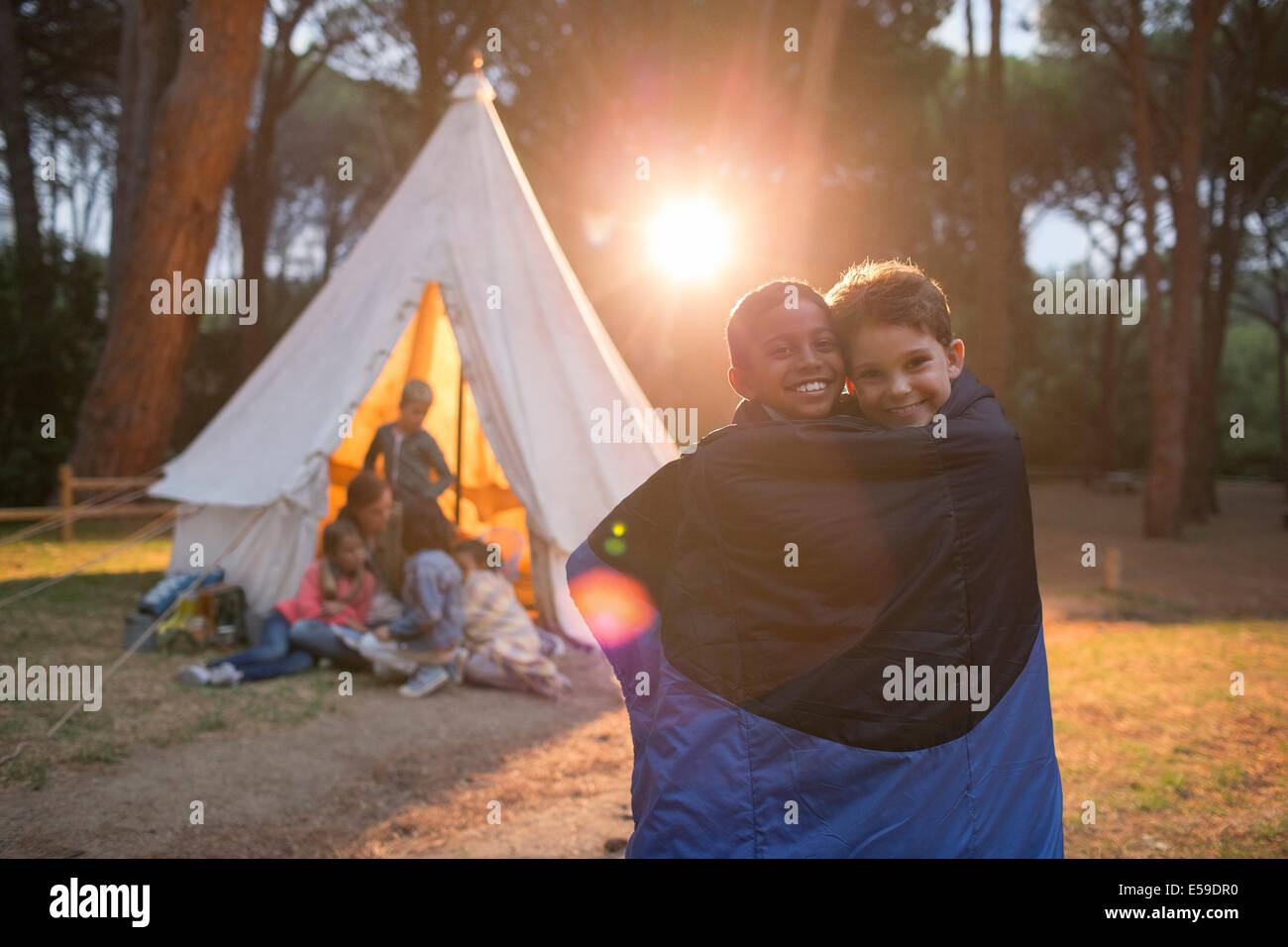 Boys wrapped in blanket at campsite - Stock Image