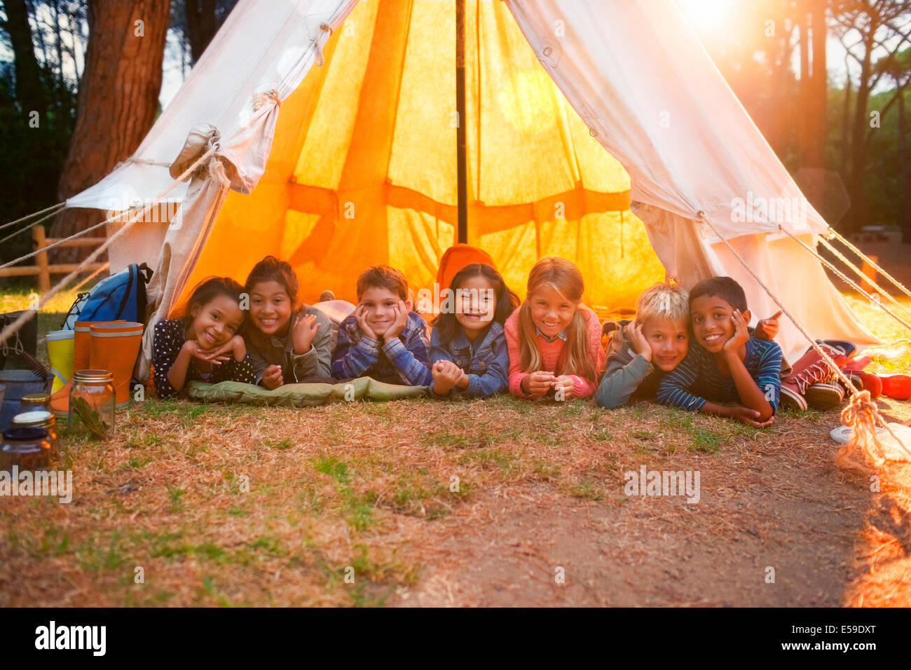 Children smiling in teepee at campsite Stock Photo