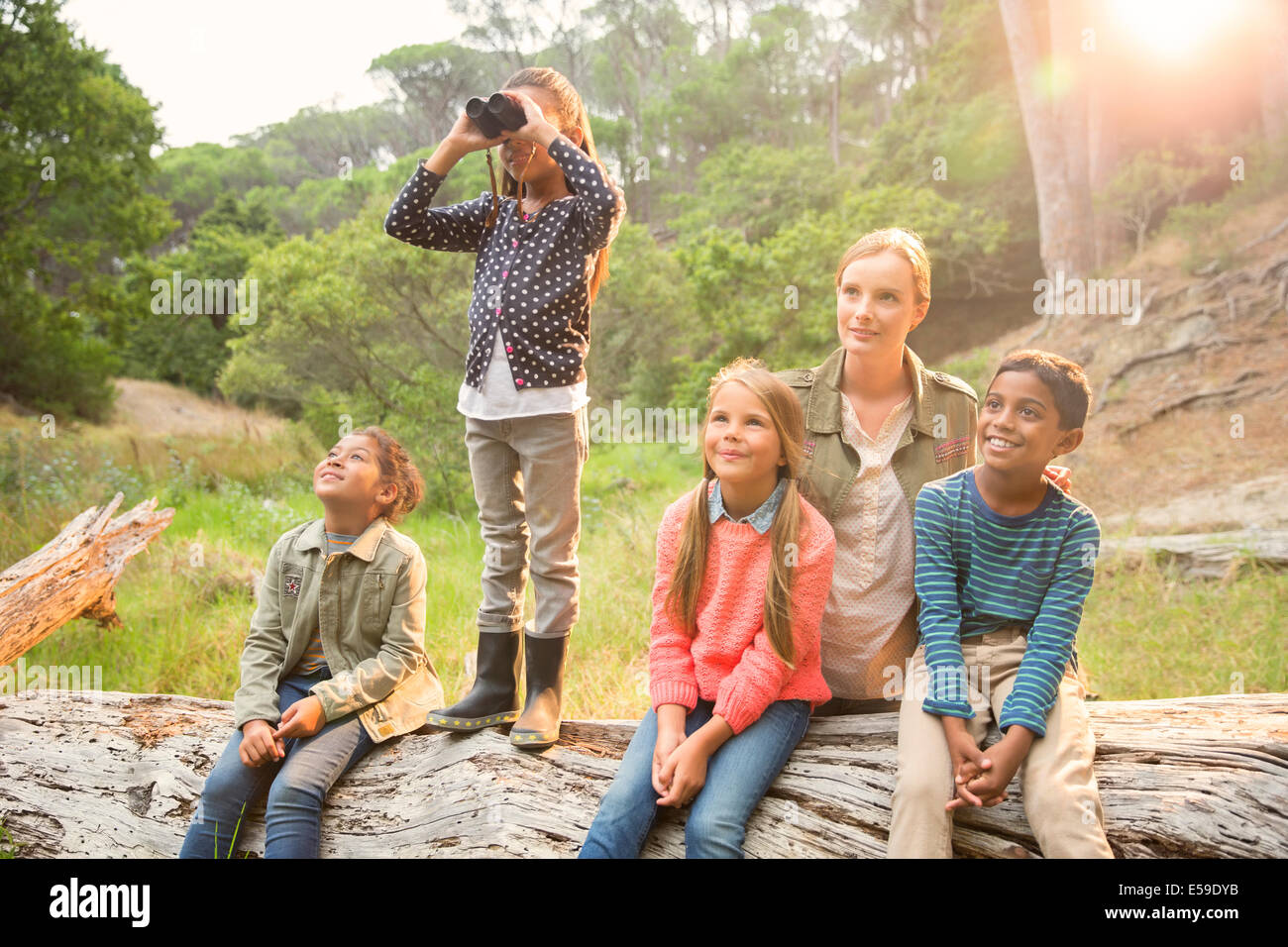 Students and teacher using binoculars in forest Stock Photo