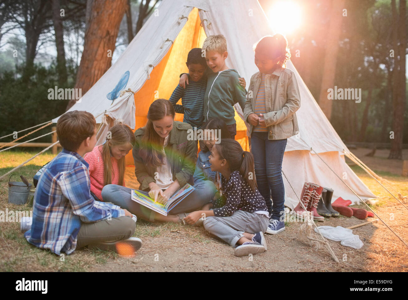 Teacher and students reading at campsite - Stock Image