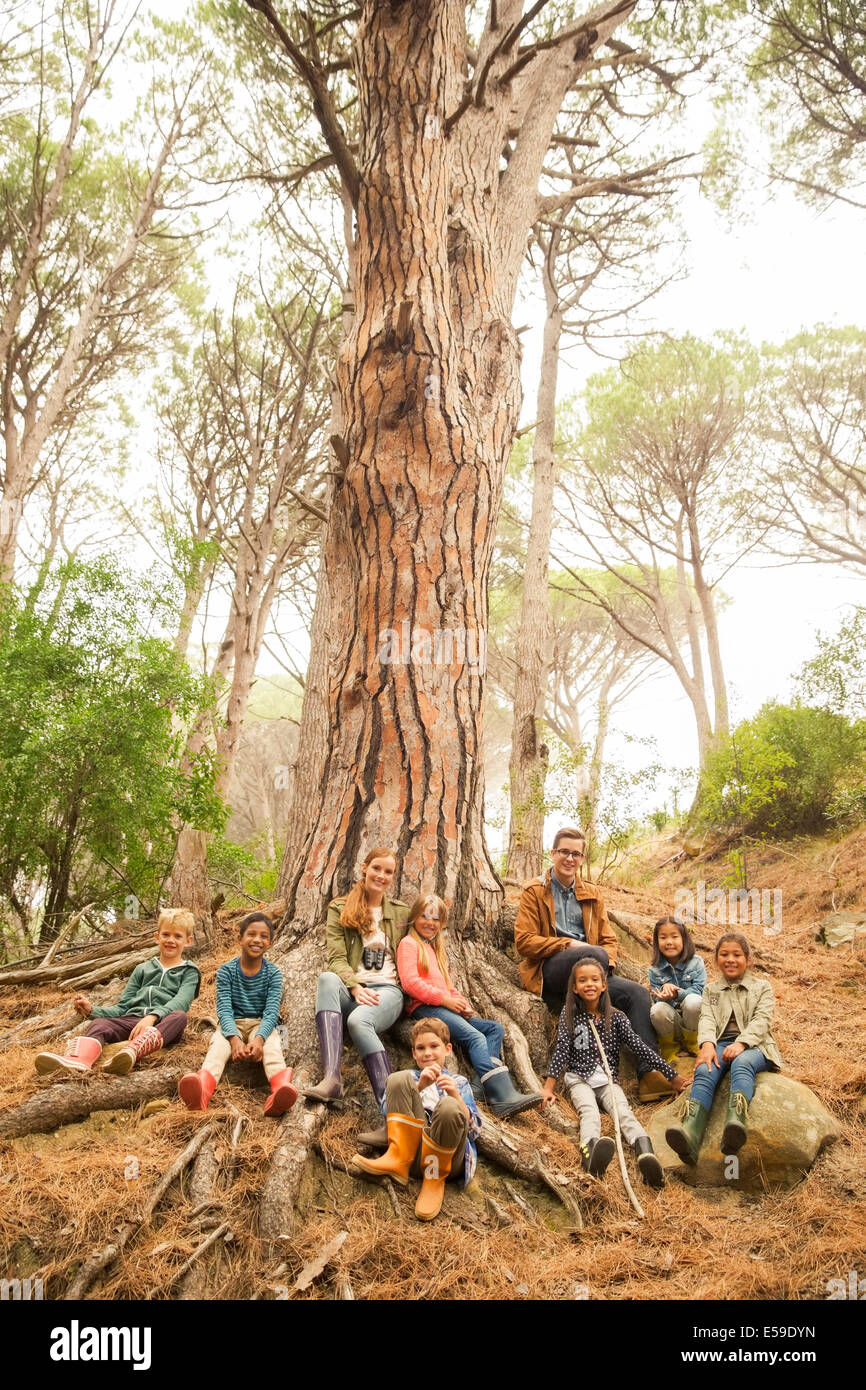 Students and teachers sitting on tree in forest - Stock Image