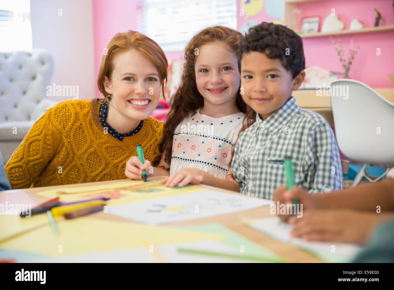 Students and teacher smiling in classroom - Stock Image