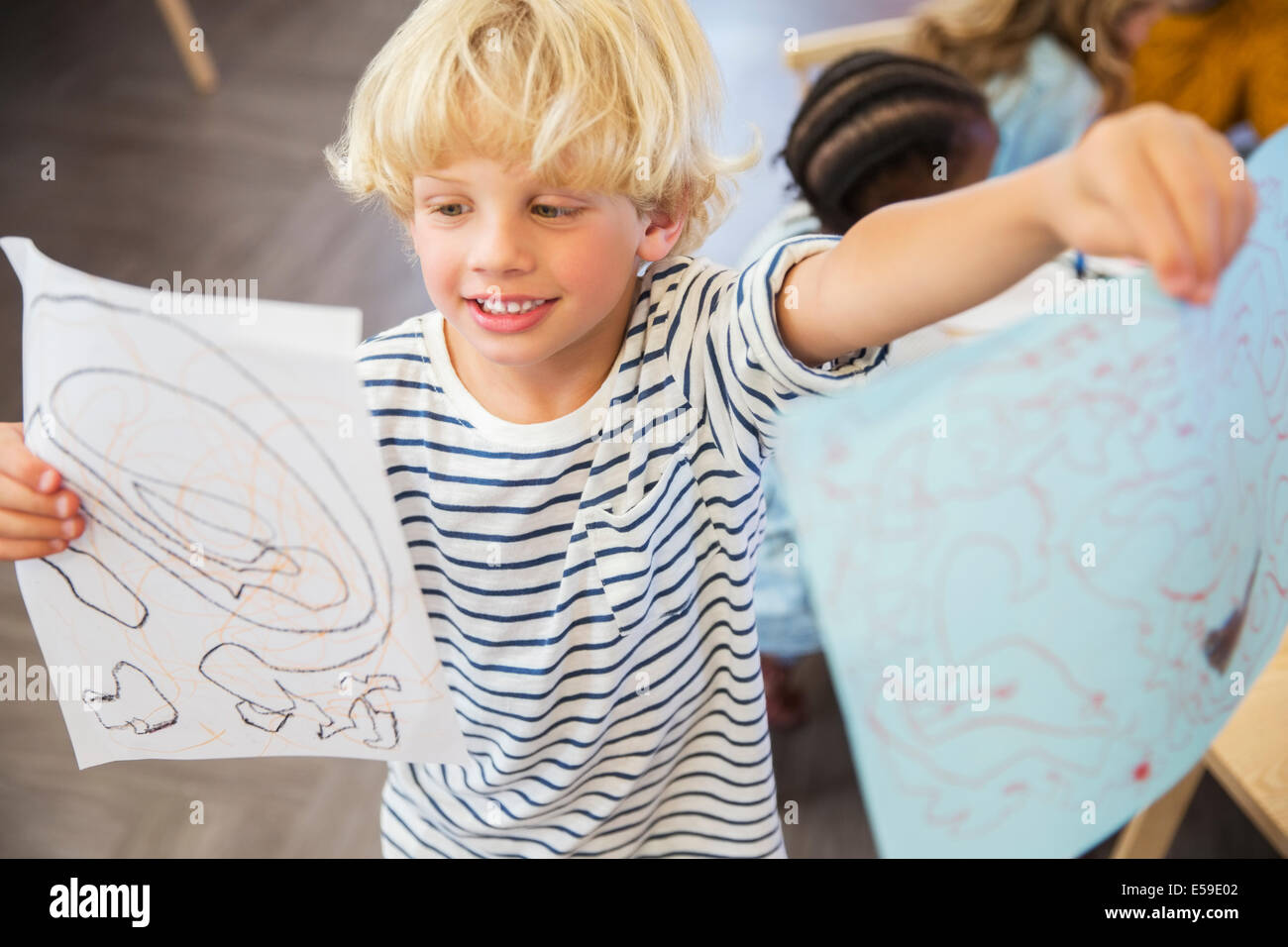 Student showing off drawings in classroom - Stock Image