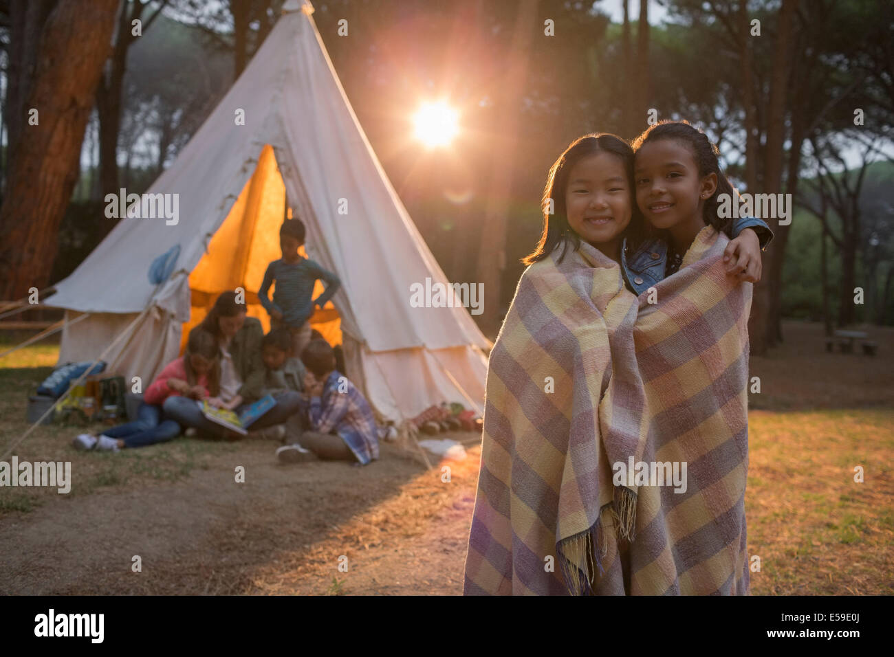 Girls wrapped in blanket at campsite - Stock Image