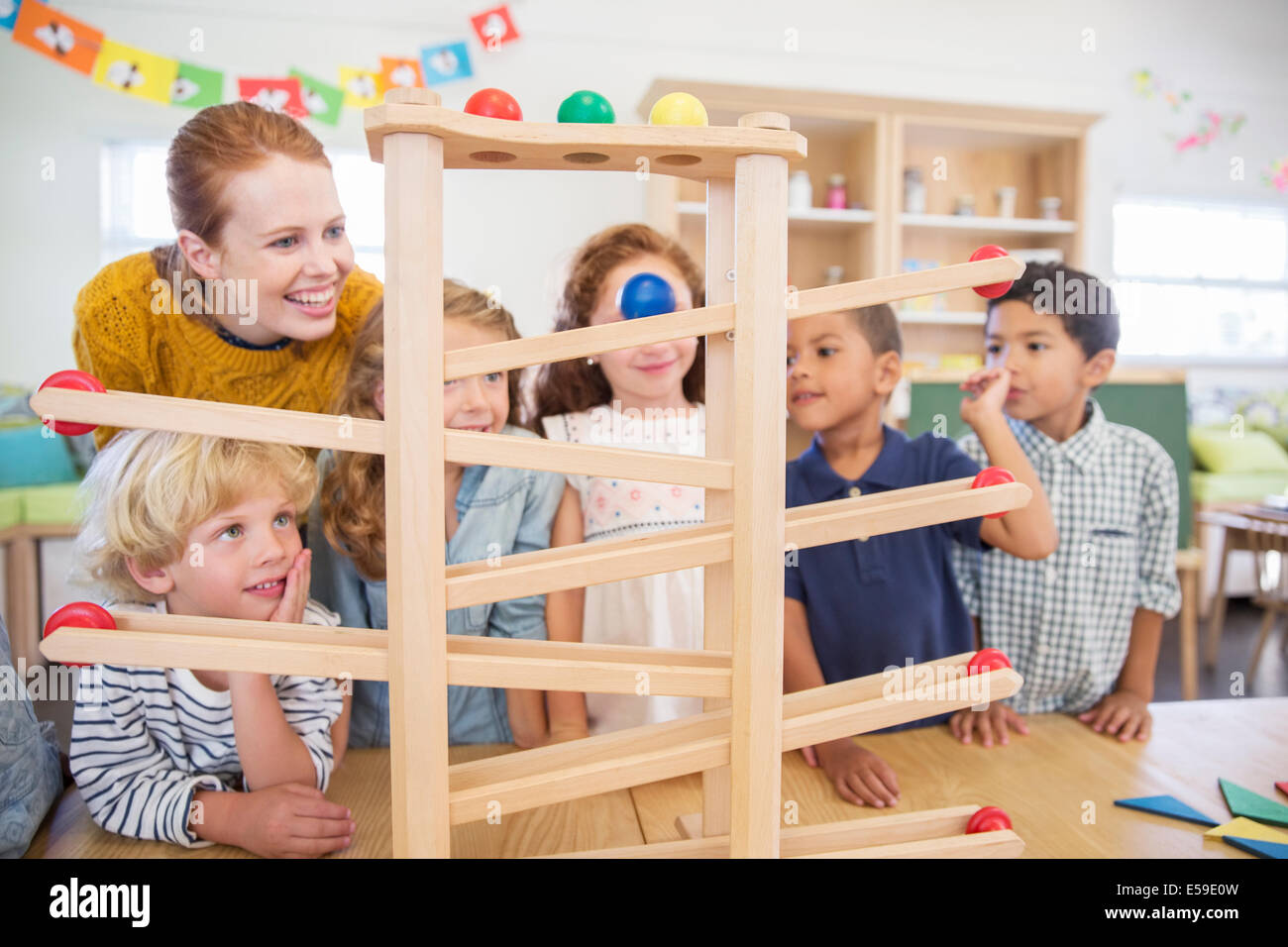 Students and teacher using model in classroom - Stock Image
