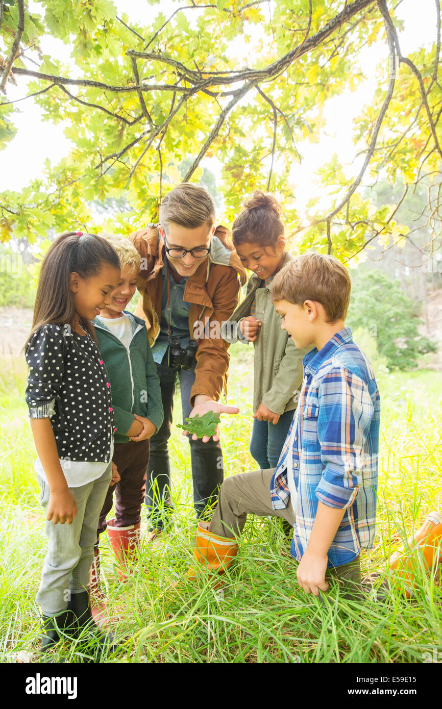 Students and teacher examining leaf outdoors - Stock Image