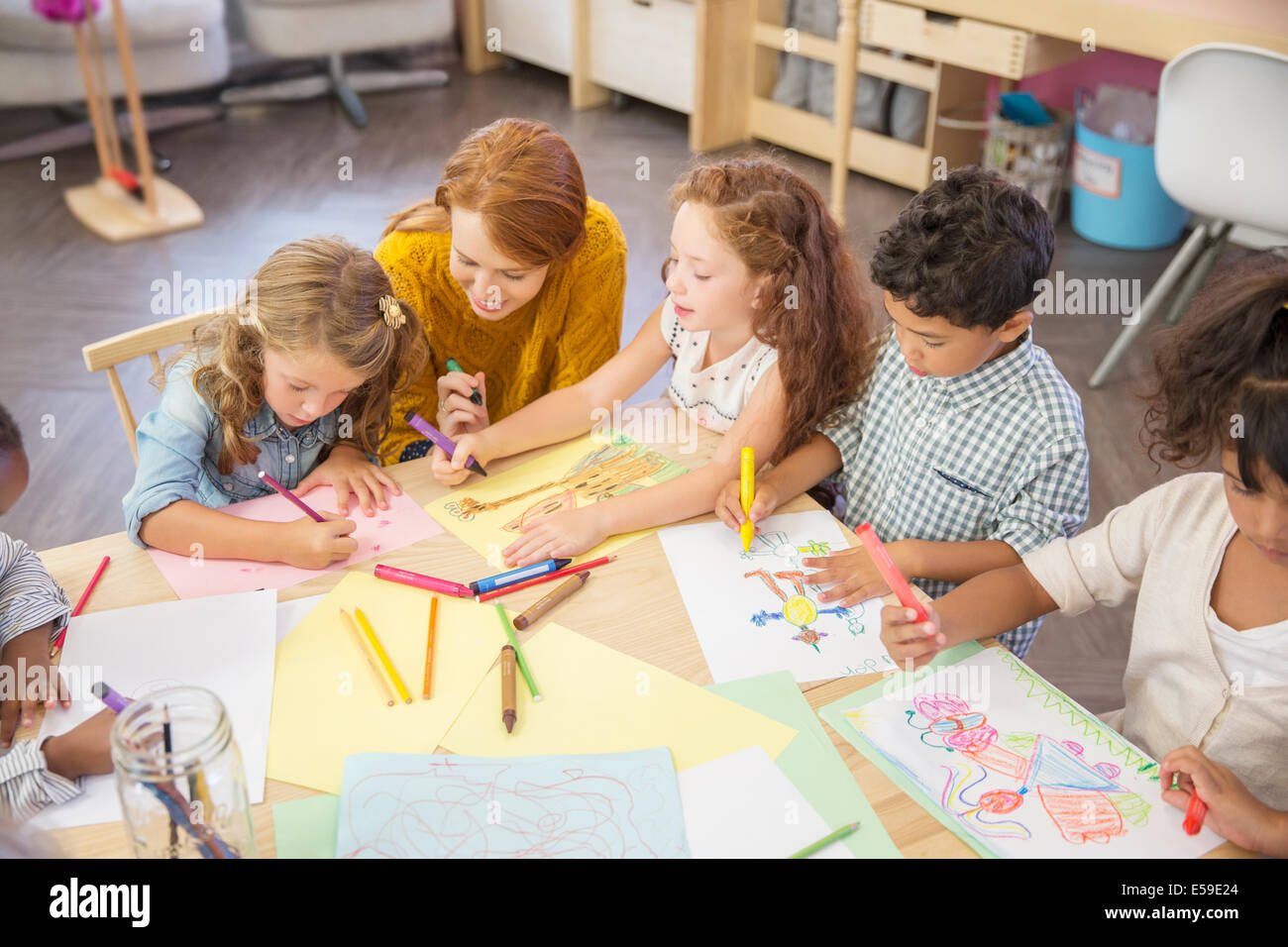 Students and teacher drawing in classroom - Stock Image