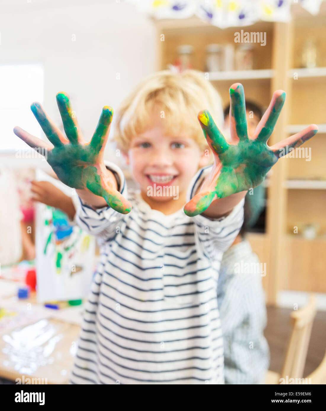 Student showing off messy hands in classroom - Stock Image