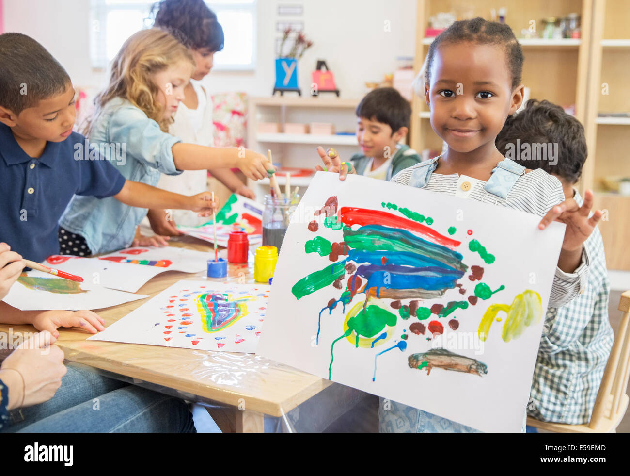 Student showing off finger painting in classroom - Stock Image