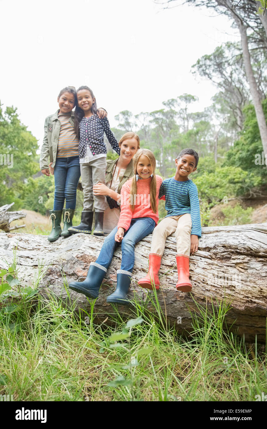 Students and teacher smiling on wooden log - Stock Image