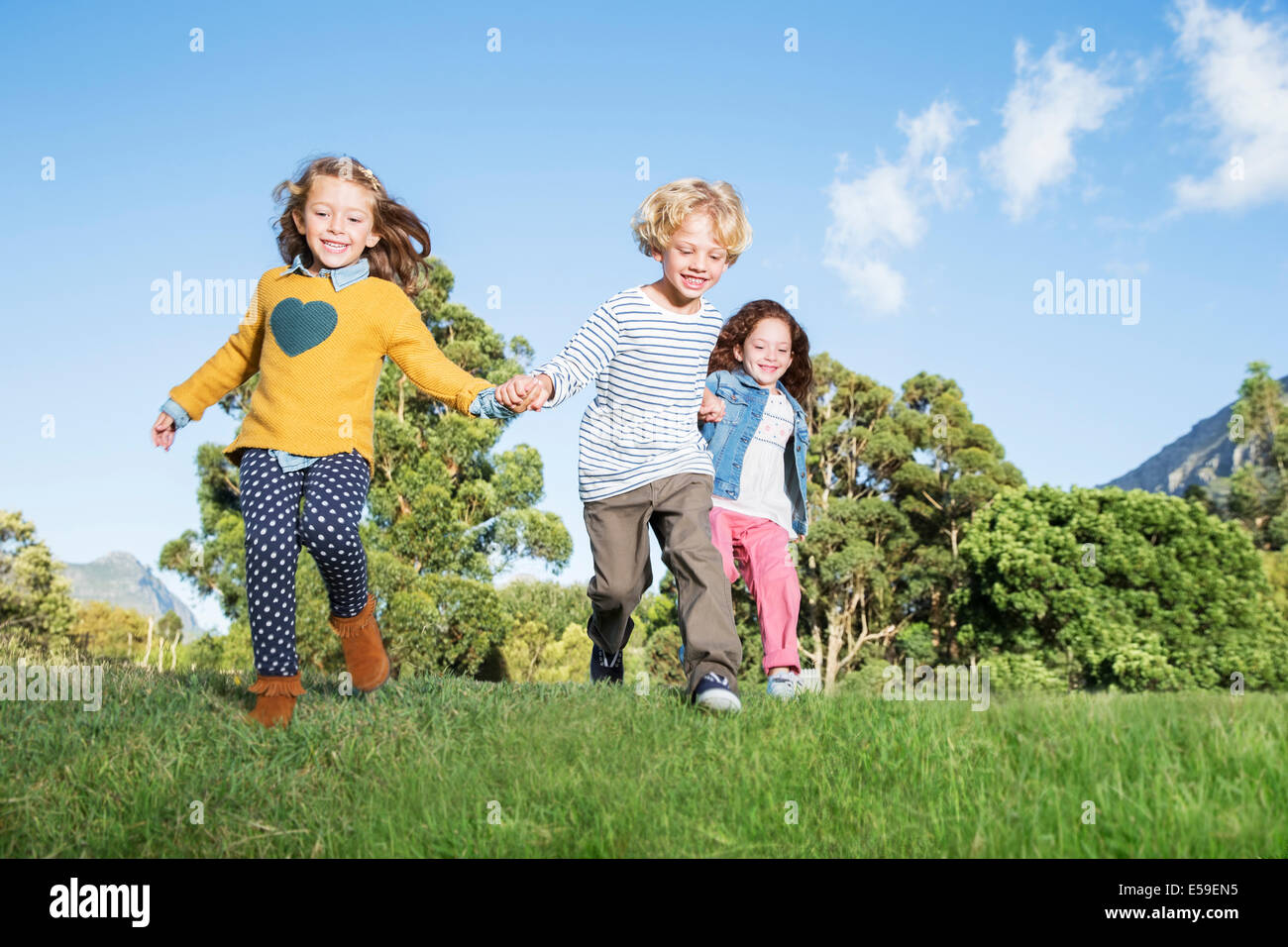 Children holding hands in field - Stock Image