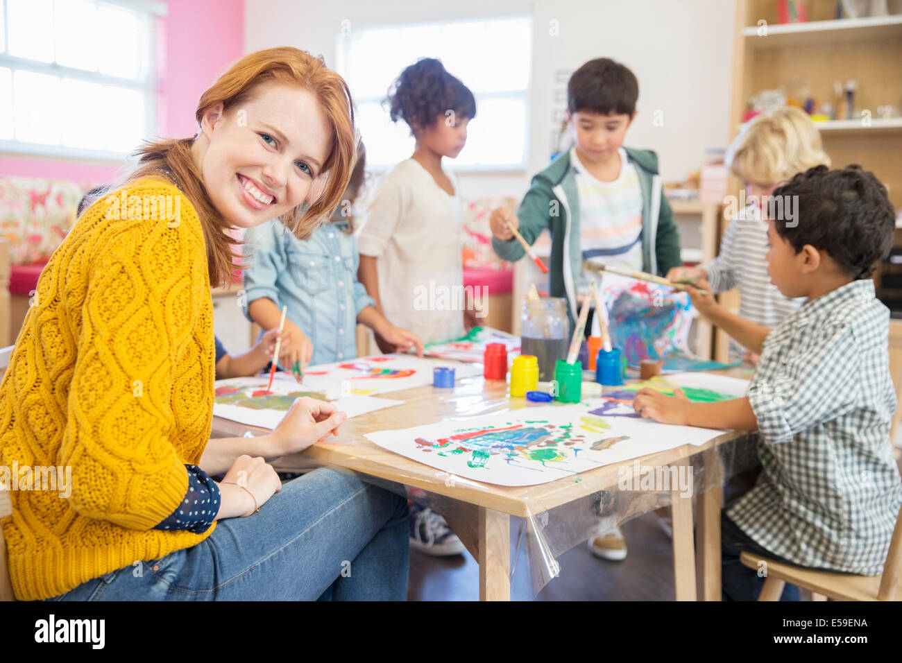 Teacher and students painting in classroom - Stock Image