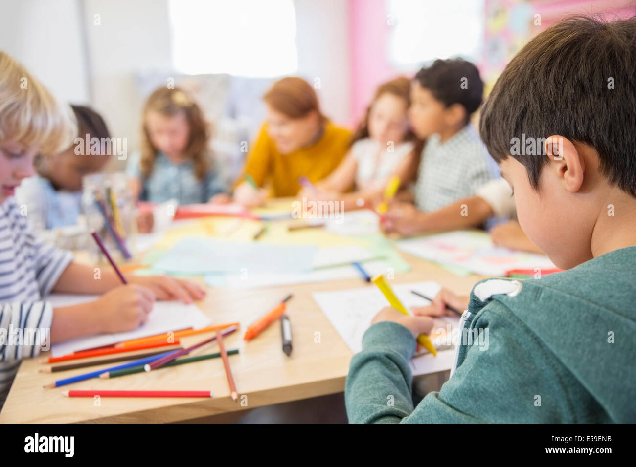 Teacher and students drawing in classroom - Stock Image