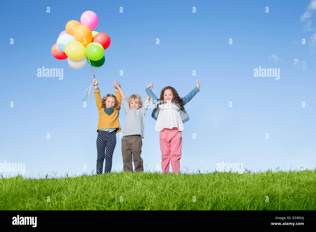 Children with balloons cheering on grassy hill - Stock Image