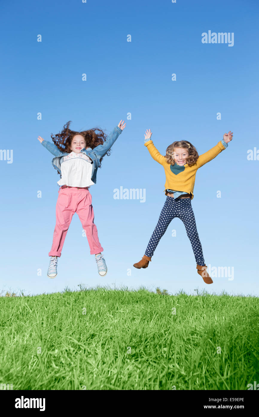 Girls jumping for joy on grassy hill - Stock Image