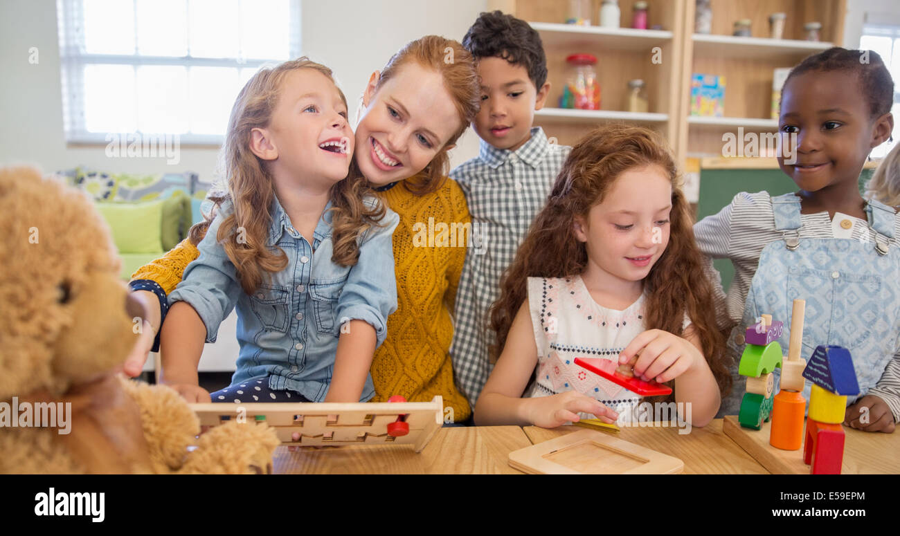 Students and teacher playing in classroom - Stock Image