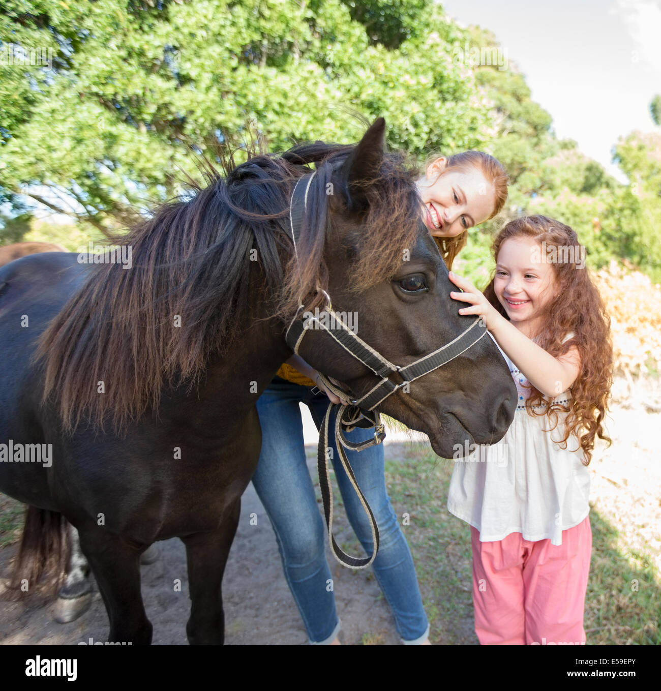 Mother and daughter petting horse outdoors - Stock Image