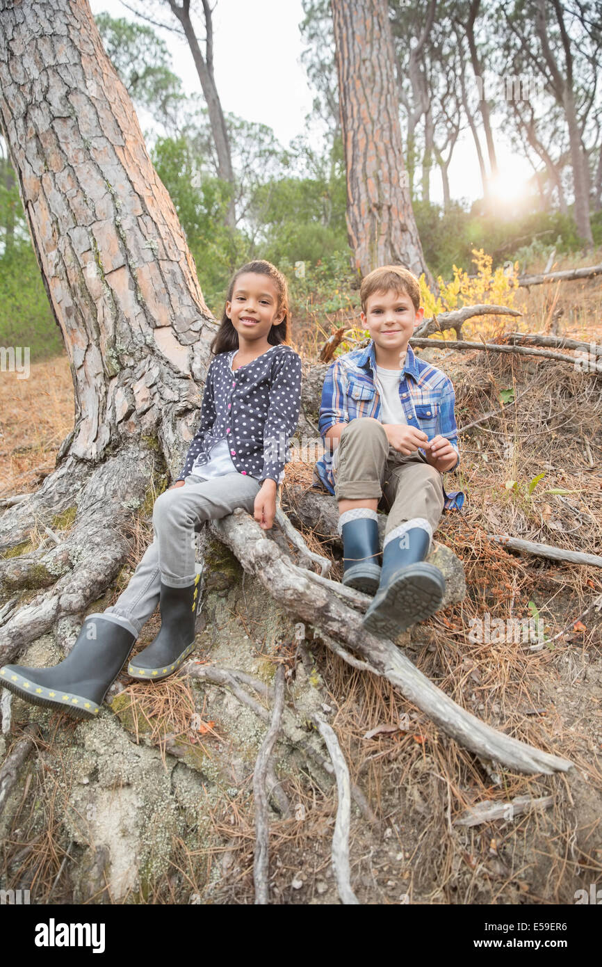 Children sitting on tree roots in forest - Stock Image