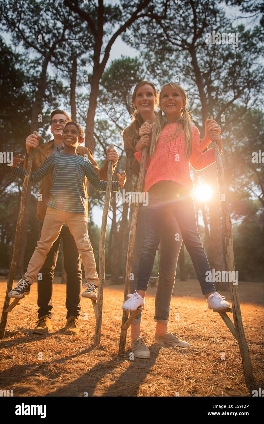 Teachers helping students walk on stilts outdoors - Stock Image