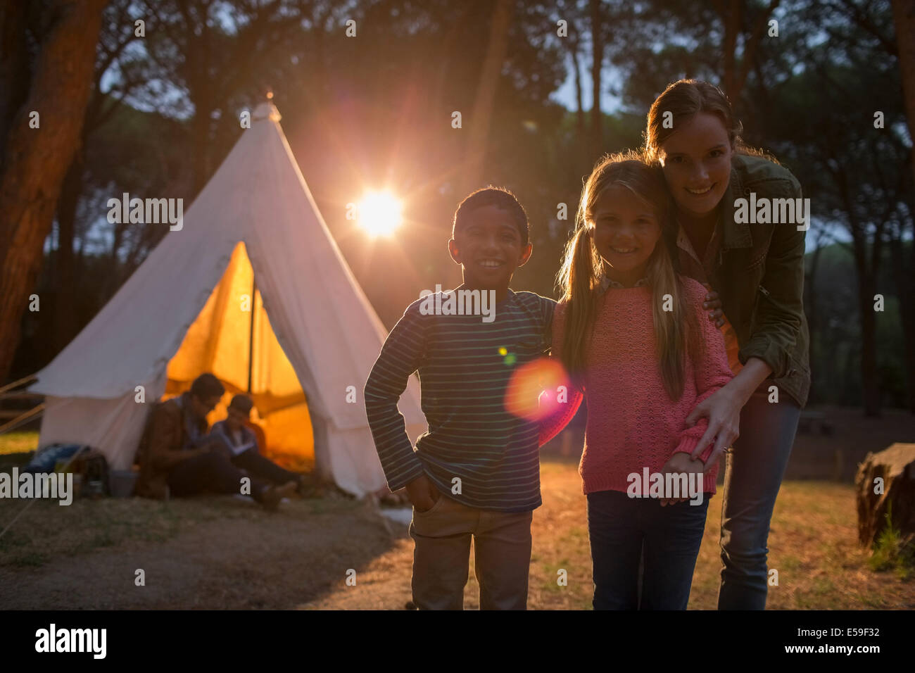 Students and teacher smiling at campsite - Stock Image