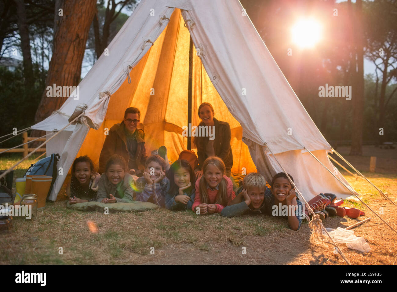 Students and teachers smiling in teepee at campsite - Stock Image