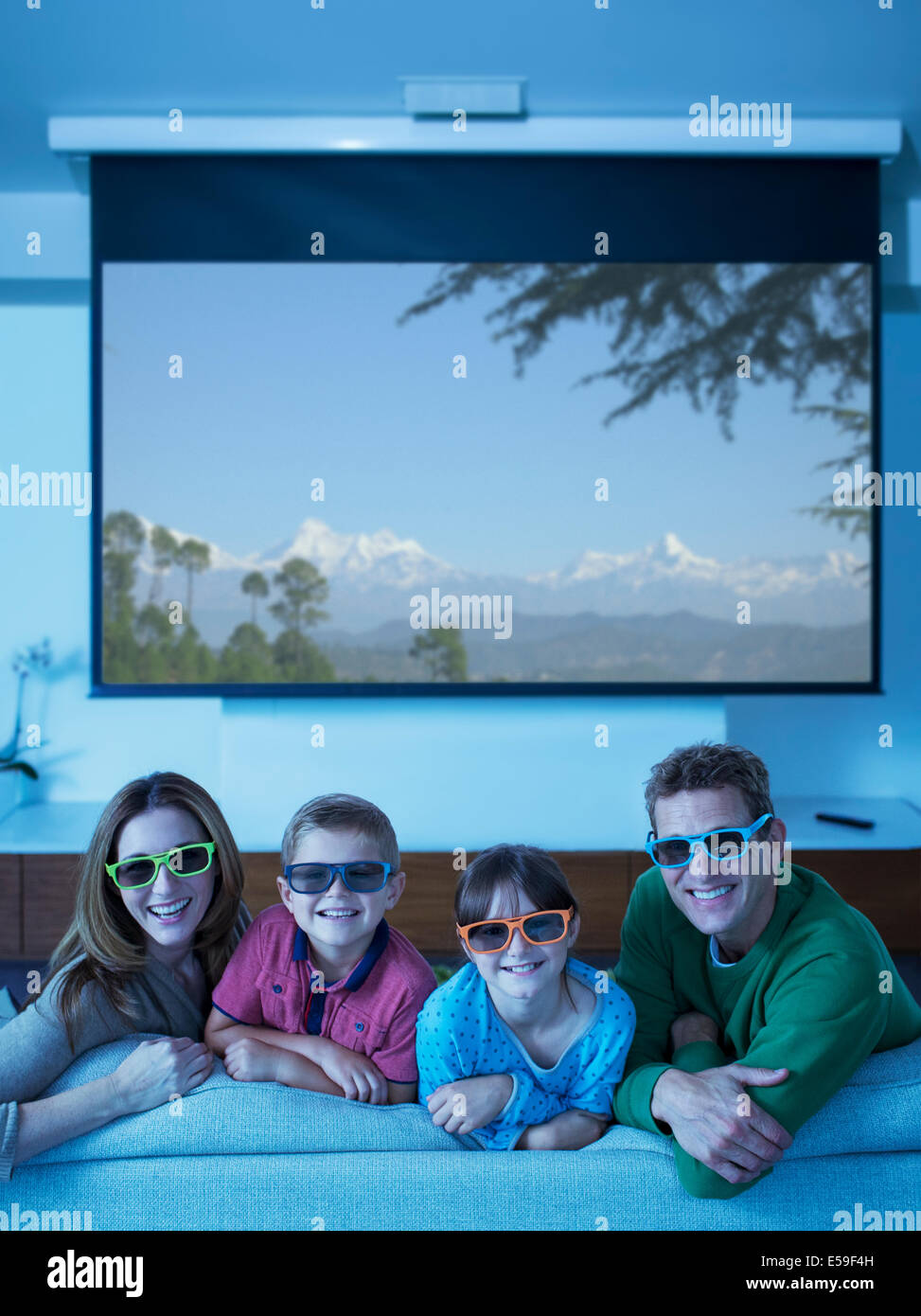 Family watching 3D television in living room - Stock Image