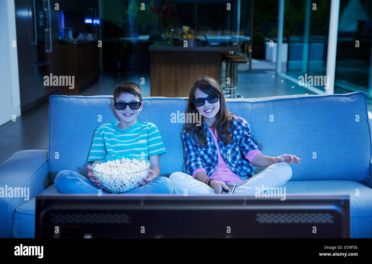 Children watching 3D television in living room - Stock Image