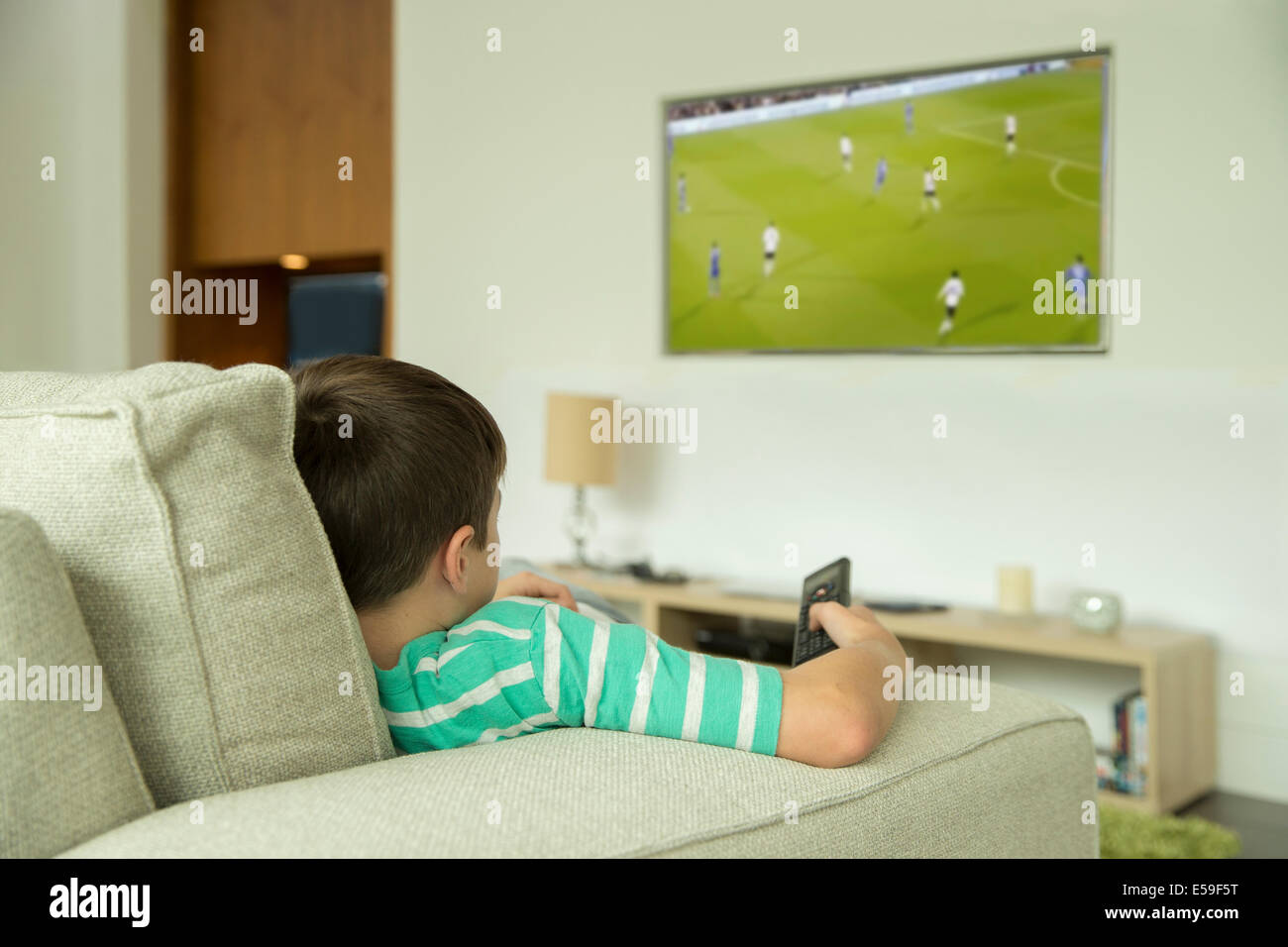 Boy watching television in living room - Stock Image